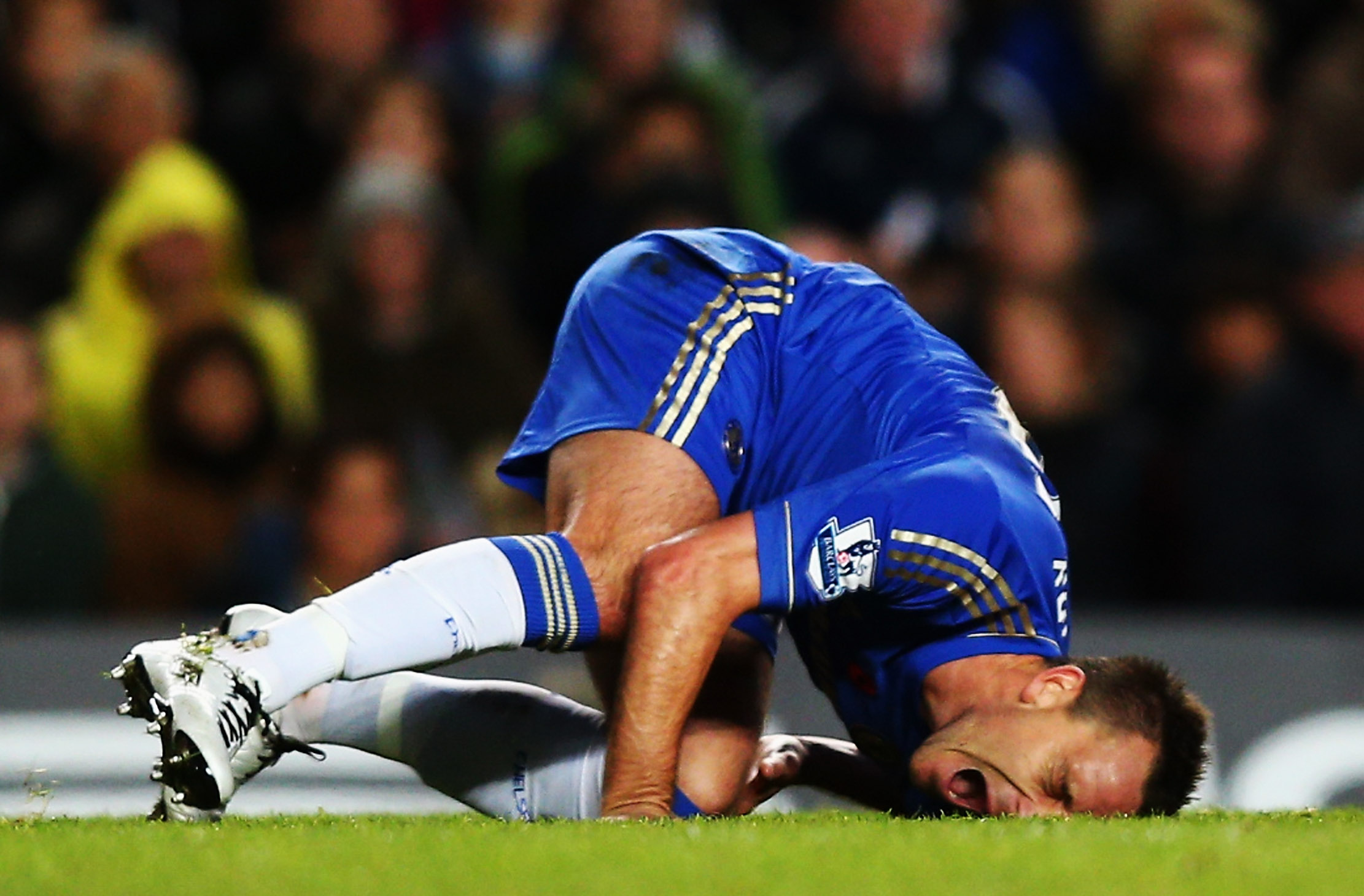 LONDON, ENGLAND - NOVEMBER 11:  John Terry of Chelsea is injured in a collision with Luis Suarez of Liverpool during the Barclays Premier League match between Chelsea and Liverpool at Stamford Bridge on November 11, 2012 in London, England.  (Photo by Cli