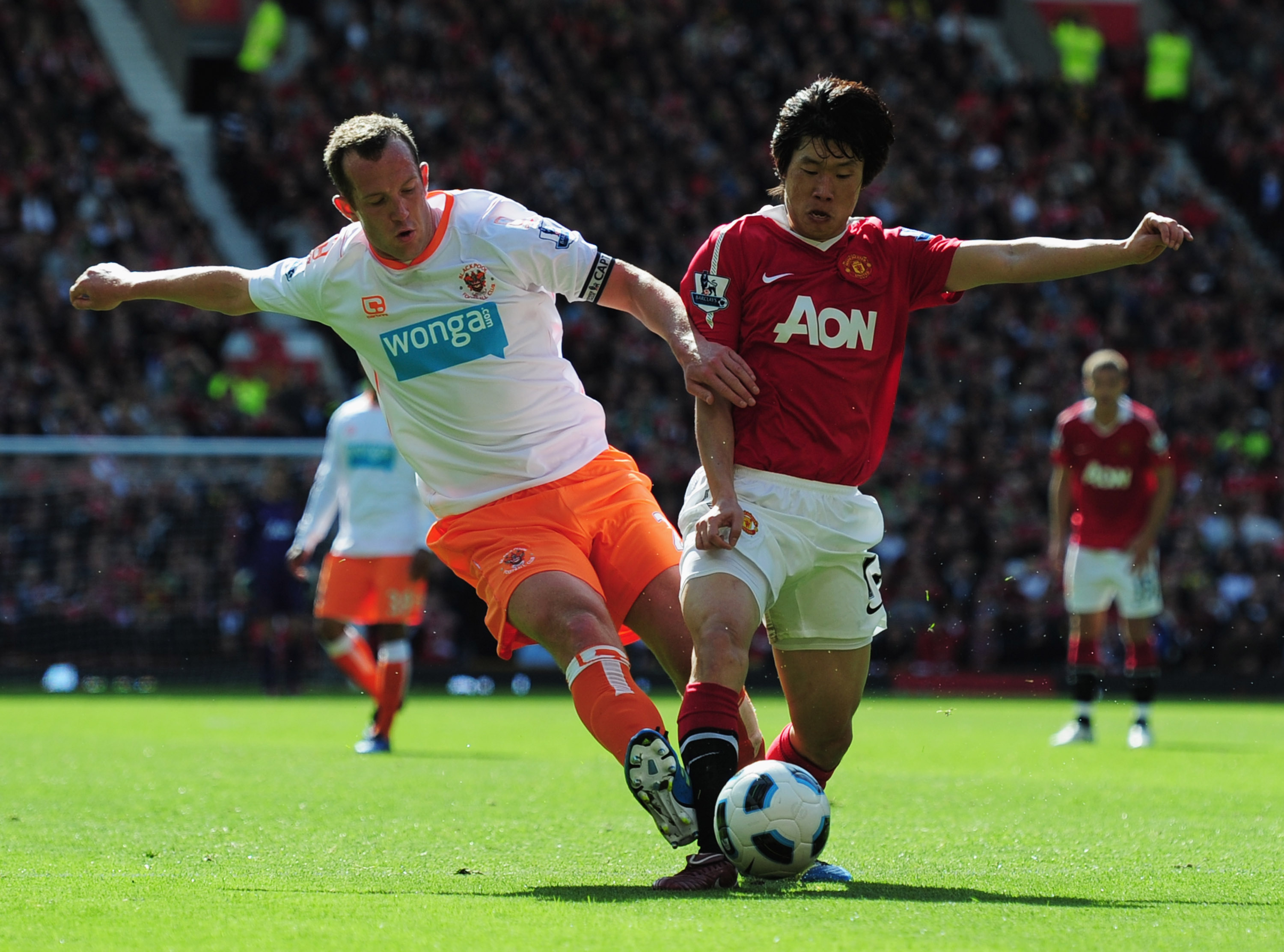 MANCHESTER, ENGLAND - MAY 22:  Park Ji-Sung of Manchester United is tackled by Charlie Adam of Blackpool during the Barclays Premier League match between Manchester United and Blackpool at Old Trafford on May 22, 2011 in Manchester, England.  (Photo by Sh