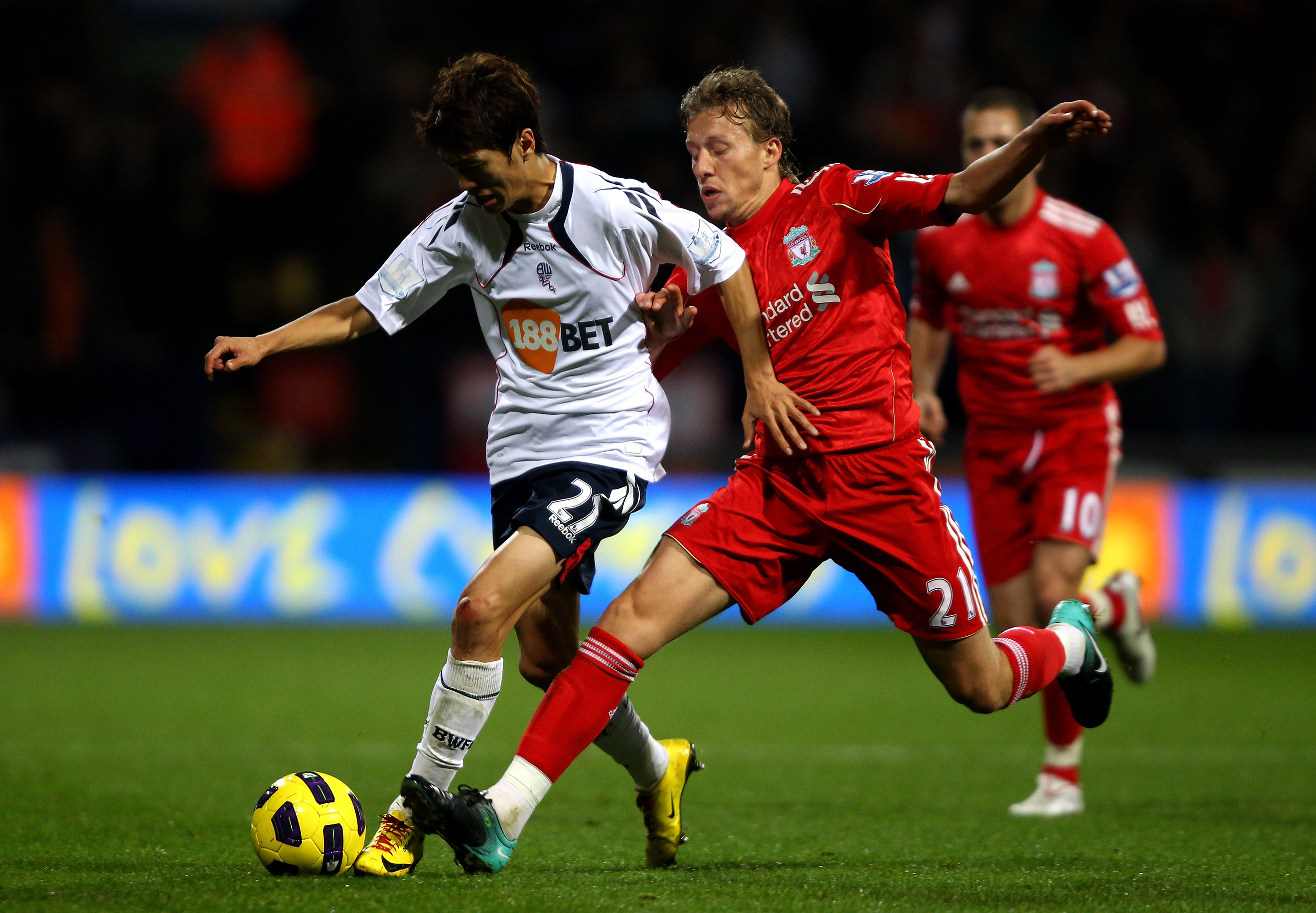 BOLTON, ENGLAND - OCTOBER 31:  Lucas of Liverpool tussles for posession with Chung Yong Lee of Bolton Wanderers during the Barclays Premier League match between Bolton Wanderers and Liverpool at the Reebok Stadium on October 31, 2010 in Bolton, England.
