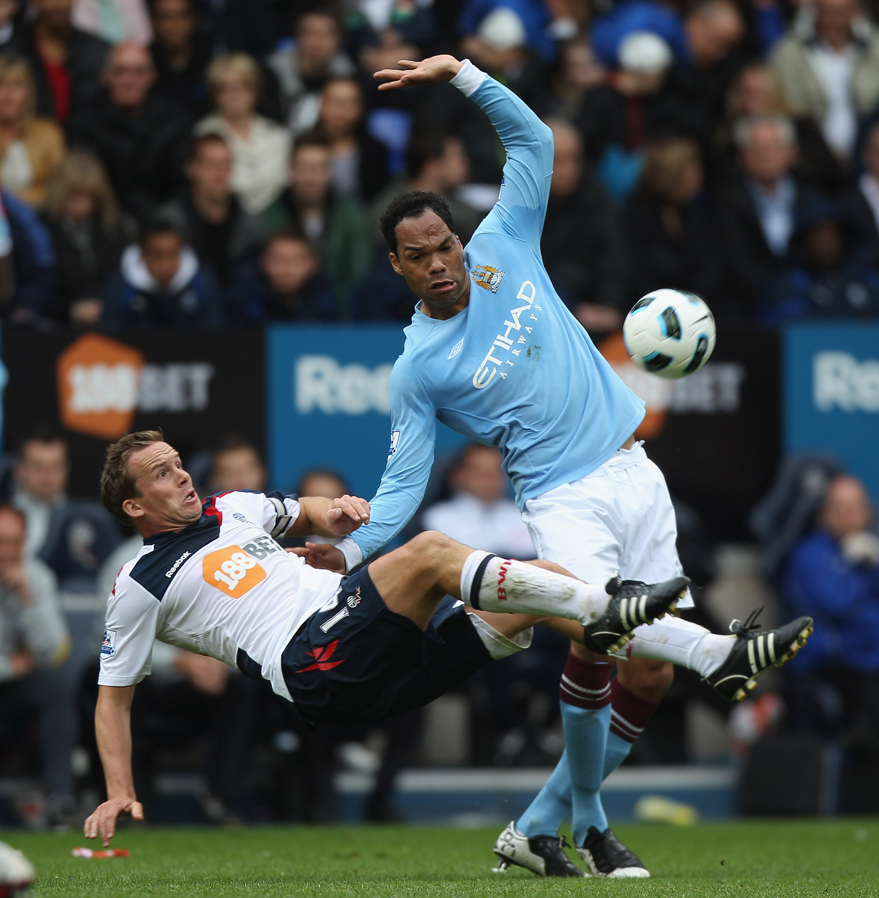 BOLTON, ENGLAND - MAY 22:  Kevin Davies (L) of Bolton falls under the challenge of Joleon Lescott (R) during the Barclays Premier League match between  Bolton Wanderers and Manchester City at the Reebok Stadium on May 22, 2011 in Bolton, England.  (Photo