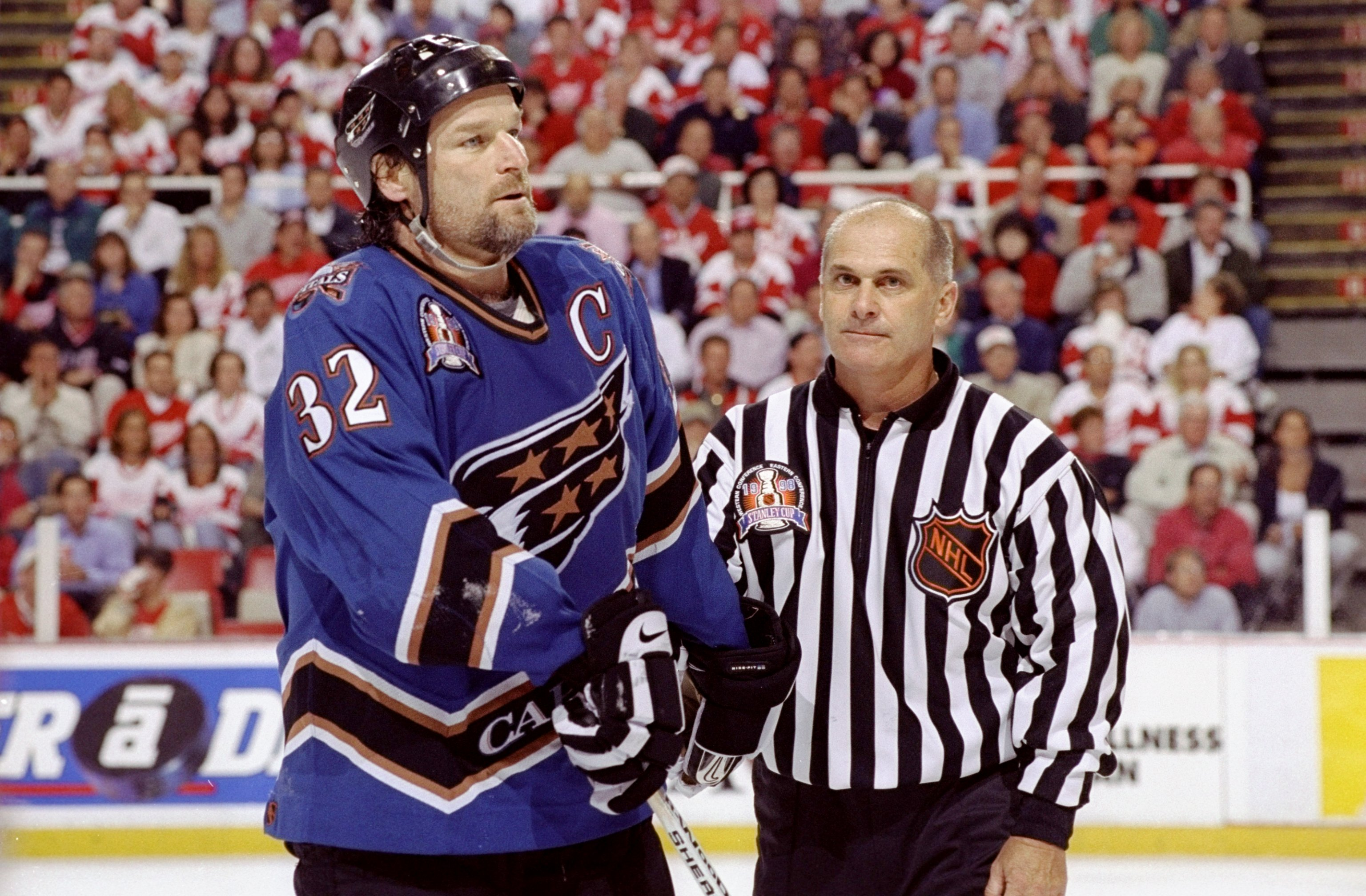 9 Jun 1998:  Dale Hunter #32 of the Washington Capitals iis escorted off by a referee during the NHL Stanley Cup Finals game against the Detroit Red Wings at the Joe Louis Arena in Detroit, Michigan. The Red Wings defeated the Capitals 2-1. Mandatory Cred
