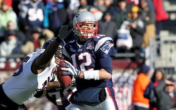 FOXBORO, MA - JANUARY 10:  Tom Brady #12 of the New England Patriots looks to pass against pressure from Terrell Suggs #55 of the Baltimore Ravens during the 2010 AFC wild-card playoff game at Gillette Stadium on January 10, 2010 in Foxboro, Massachusetts