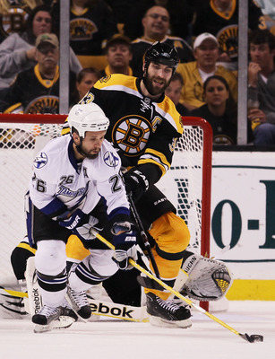 BOSTON, MA - MAY 23:  Martin St. Louis #26 of the Tampa Bay Lightning and Zdeno Chara #33 of the Boston Bruins vie for the puck in Game Five of the Eastern Conference Finals during the 2011 NHL Stanley Cup Playoffs at TD Garden on May 23, 2011 in Boston,