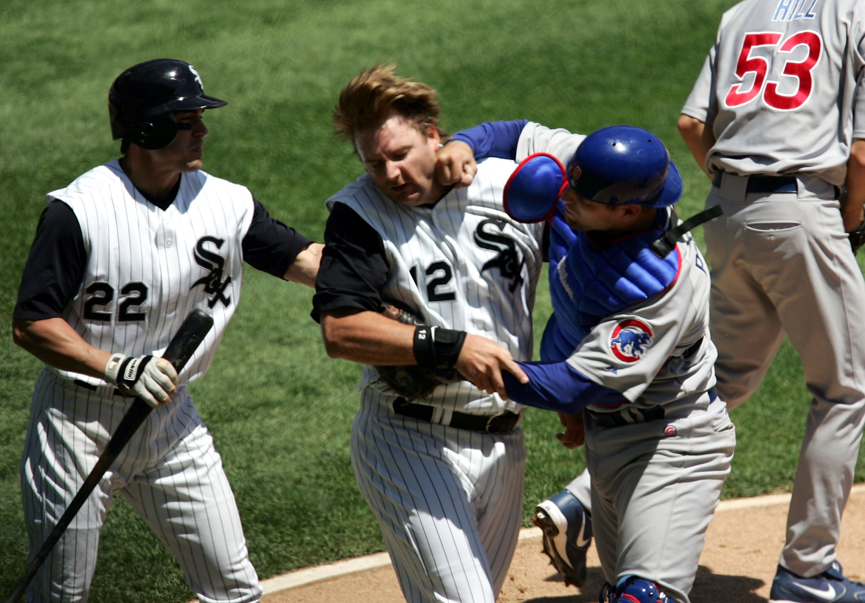 CHICAGO - MAY 20:  Michael Barrett #8 of the Chicago Cubs punches A.J. Pierzynski #12 of the Chicago White Sox after a second inning collision as Scott Podsednik #22 steps in on May 20, 2006 at U.S. Cellular Field in Chicago, Illinois.  (Photo by Jonathan