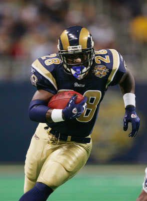 ST. LOUIS - NOVEMBER 7:   Running back Marshall Faulk #28 of the St. Louis Rams runs upfield against the New England Patriots on November 7, 2004 at the Edward Jones Dome in St. Louis, Missouri. The Patriots defeated the Rams 40-22. (Photo by Elsa/Getty I
