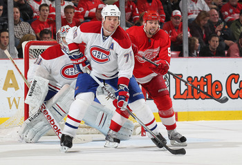 DETROIT,MI - DECEMBER 10:  Hal Gill #75 of the Montreal Canadiens works to keep Tomas Holmstrom #96 of the Detroit Red Wings in check in a game on December 10, 2010 at the Joe Louis Arena in Detroit, Michigan. The Wings defeated the Canadiens 4-2. (Photo
