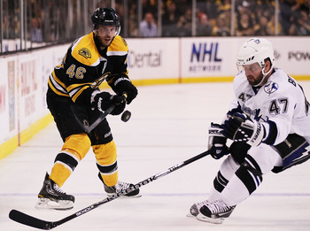 BOSTON, MA - MAY 23:  David Krejci #46 of the Boston Bruins and Marc-Andre Bergeron #47 of the Tampa Bay Lightning vie for the puck in Game Five of the Eastern Conference Finals during the 2011 NHL Stanley Cup Playoffs at TD Garden on May 23, 2011 in Bost