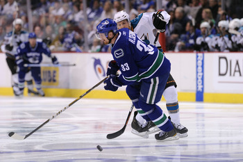 VANCOUVER, CANADA - MAY 24:  Joe Pavelski #8 of the San Jose Sharks pokes the puck past Henrik Sedin #33 of the Vancouver Canucks in the third period in Game Five of the Western Conference Finals during the 2011 Stanley Cup Playoffs at Rogers Arena on May