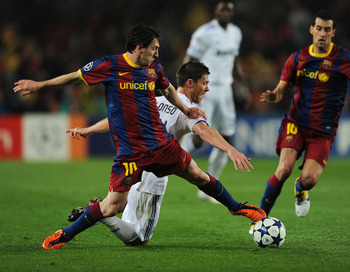 BARCELONA, SPAIN - MAY 03:  Lionel Messi (L) of Barcelona duels for the ball with Xabi Alonso of Real Madrid during the UEFA Champions League Semi Final second leg match between Barcelona and Real Madrid at the Camp Nou stadium on May 3, 2011 in Barcelona