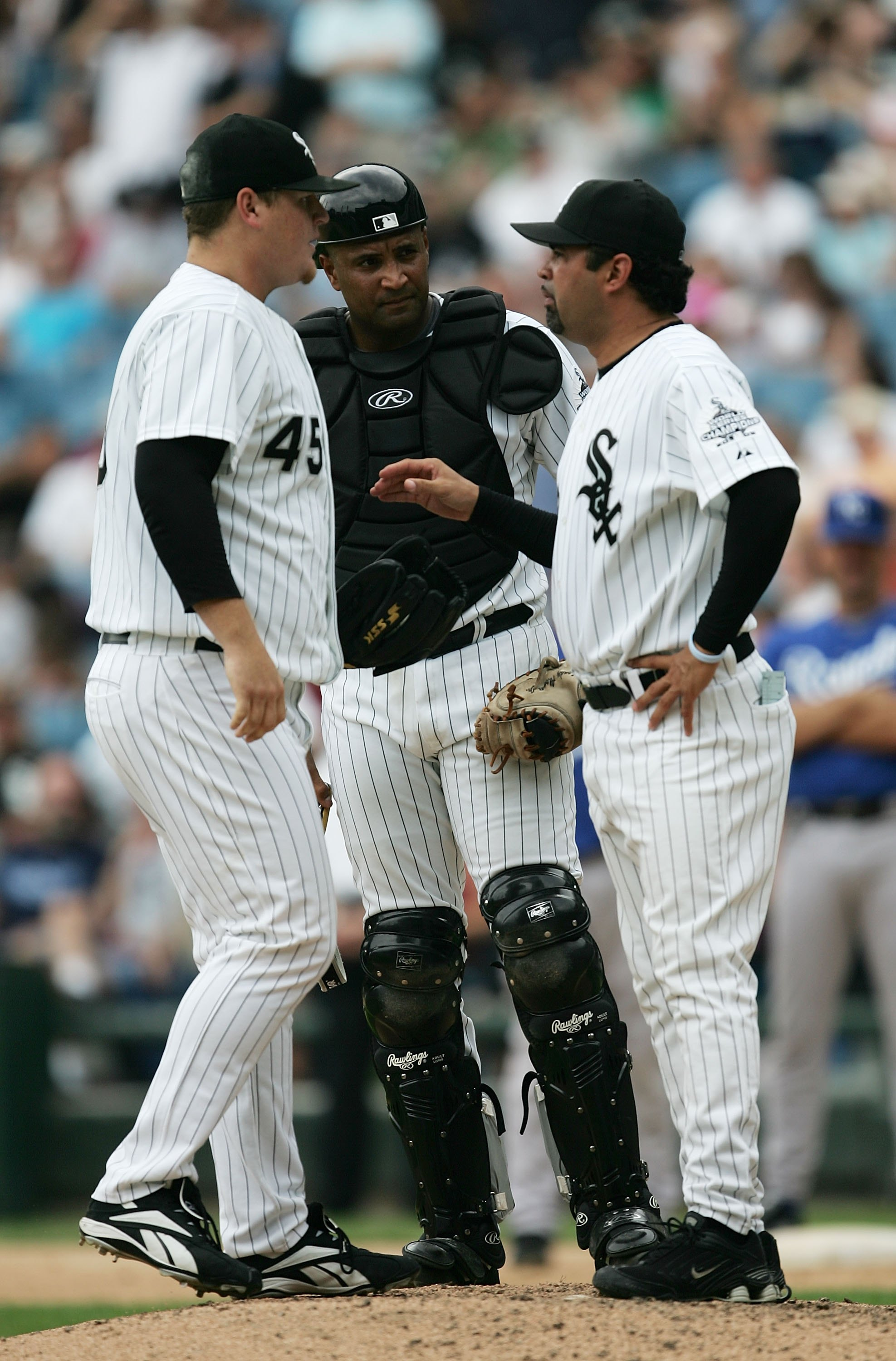 CHICAGO - AUGUST 17:  Manager Ozzie Guillen #13 of the Chicago White Sox (R) talks with catcher Sandy Alomar, Jr. #26 and closer Bobby Jenks #45 in the eighth inning of a game against the Kansas City Royals August 17, 2006 at U.S. Cellular Field in Chicag