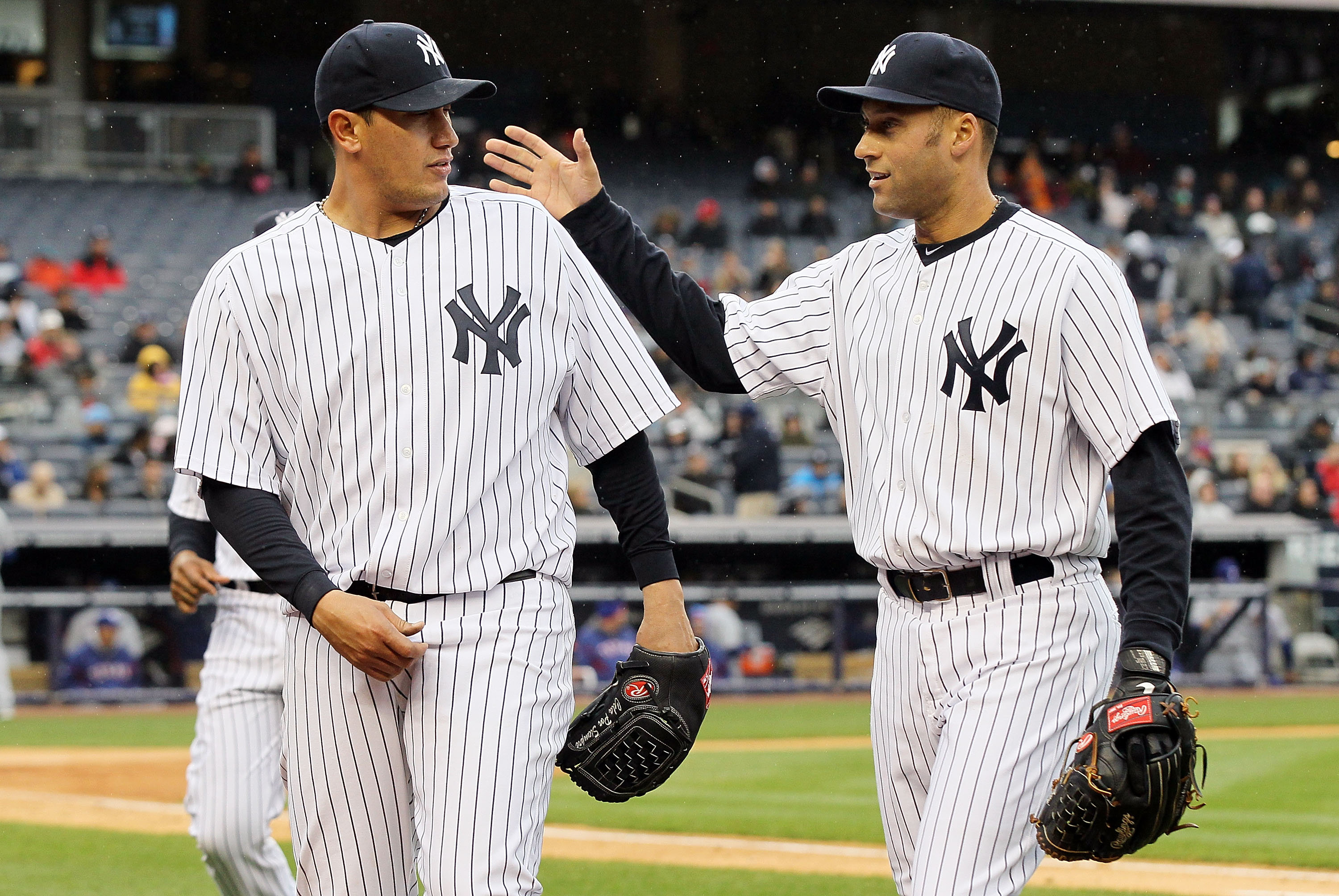 NEW YORK, NY - APRIL 16:  Freddy Garcia #36 and Derek Jeter #2 of the New York Yankees celebrate the final out of an inning against the Texas Rangers on April 16, 2011 at Yankee Stadium in the Bronx borough of New York City.  (Photo by Jim McIsaac/Getty I