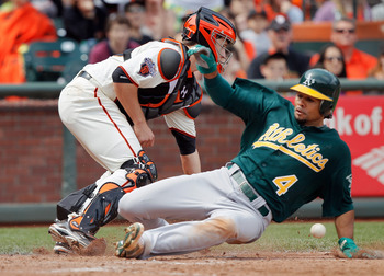 SAN FRANCISCO, CA - MAY 22:  Coco Crisp #4 of the Oakland A's scores a go-ahead run from second base ahead of the throw to catcher Buster Posey #28 of the San Francisco Giants on a single by Daric Barton in the seventh inning at AT&T Park on May 22, 2011