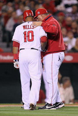 ANAHEIM, CA - MAY 09:  Vernon Wells #10 of the Los Angeles Angels of Anaheim is helped off the field by manager Mike Scioscia after Wells strained his groin while at bat against the Chicago White Sox in the fourth inning at Angel Stadium of Anaheim on May