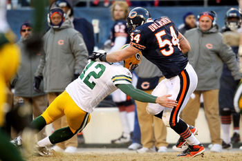 CHICAGO, IL - JANUARY 23:  Linebacker Brian Urlacher #54 of the Chicago Bears is tackled by quarterback Aaron Rodgers #12 of the Green Bay Packers after Urlacher runs an interception 39-yards in the third quarter in the NFC Championship Game at Soldier Fi