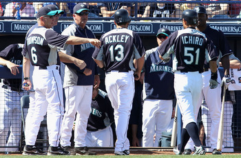 PEORIA, AZ - MARCH 04:  Dustin Ackley #13 of the Seattle Mariners is congratulated by teammates after scoring a run on a sacrifice fly hit by Ichiro Suzuki #51 during the third inning of the spring training game against the Cincinnati Reds at Peoria Stadi