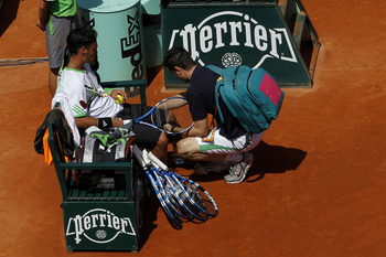PARIS, FRANCE - MAY 29:  Fabio Fognini of Italy receives treatment from ATP physiotherapist Hugo Gravil during the men's singles round four match between Fabio Fognini of Italy and Albert Montanes of Spain on day eight of the French Open at Roland Garros