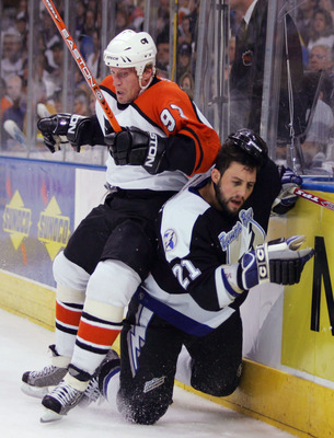 TAMPA, FL - MAY 18:  Jeremy Roenick #97 of the Philadelphia Flyers checks Cory Sarich #21 of the Tampa Bay Lightning into the boards in game five of the NHL Eastern Conference Finals during the Stanley Cup Playoffs on May 18, 2004 at the St. Pete Times Fo