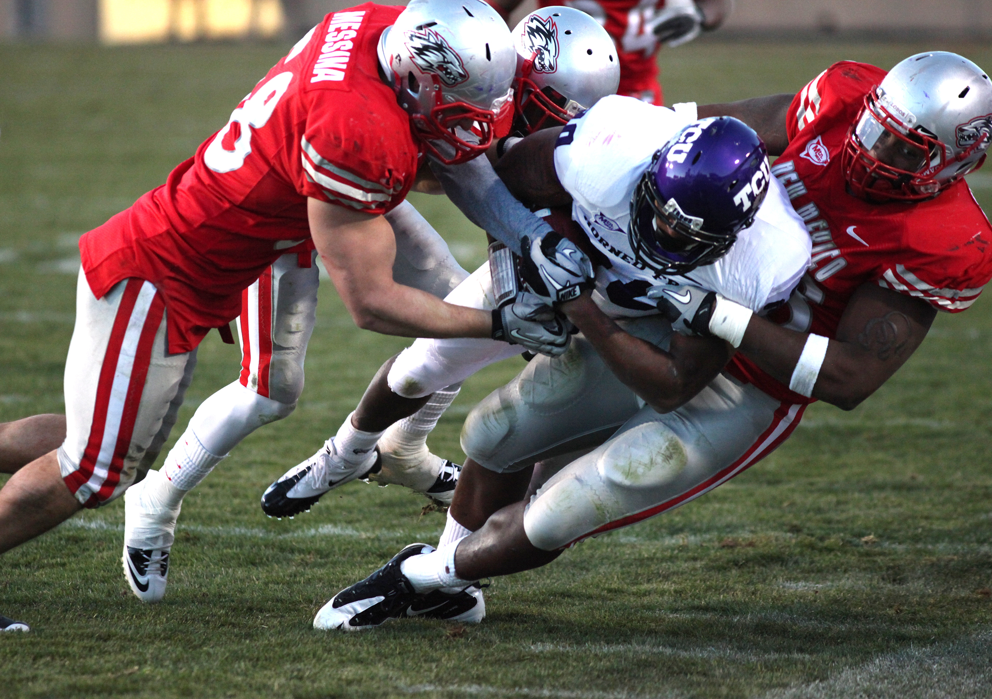 ALBUQUERQUE, NM - NOVEMBER 27: Aundre Dean #30 of the TCU Horned Frogs carries the ball against Carmen Messina #58 (L) and Jaymar Latchison #48 of the New Mexico Lobos in the 3rd quarter on November 27, 2010 at University Stadium in Albuquerque, New Mexic