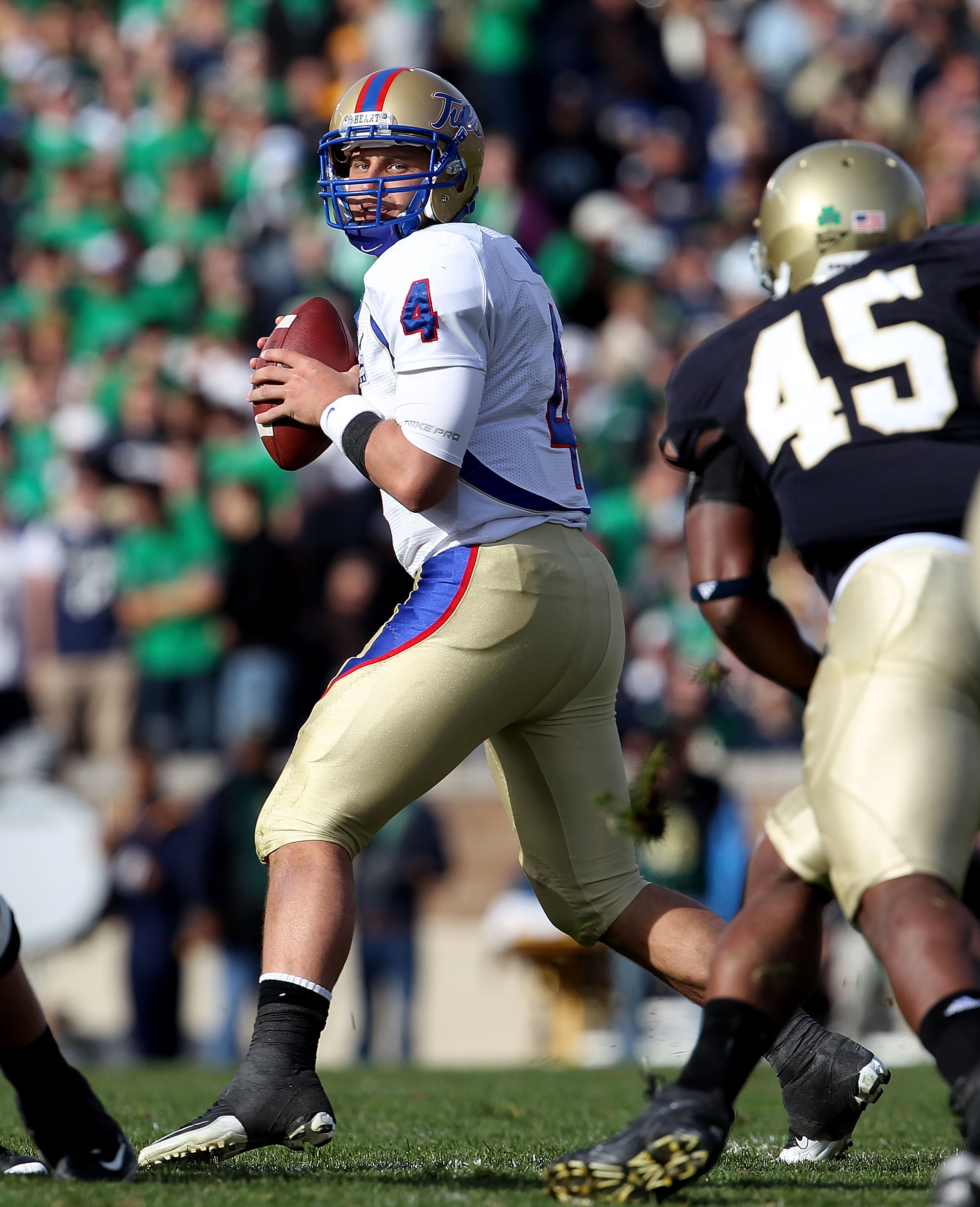 SOUTH BEND, IN - OCTOBER 30: G.J. Kinne #4 of the Tulsa Golden Hurricane looks to pass as Darius Flemming #45 of the Notre Dame Fighting Irish rushes at Notre Dame Stadium on October 30, 2010 in South Bend, Indiana. Tulsa defeated Notre Dame 28-27. (Photo