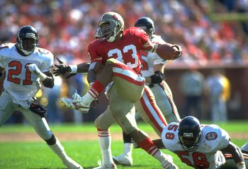 23 SEP 1990:  SAN FRANCISCO 49ERS RUNNING BACK ROGER CRAIG #33 HIGH STEPS THROUGH ATLANTA FALCONS LINEBACKER JESSIE TUGGLE #58 AND DEFENSIVE BACK DEION SANDERS #21, DURING THE 49ERS 19-13 WIN AT CANDLESTICK PARK IN SAN FRANCISCO, CALIFORNIA.