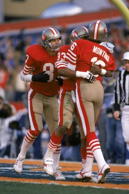 STANFORD, CA - JANUARY 20:  Quarterback Joe Montana #16 of the San Francisco 49ers congratulates teammate running back Roger Craig #33 after his eight yard touchdown reception in Super Bowl XIX against the Miami Dolphins at Stanford Stadium on January 20,
