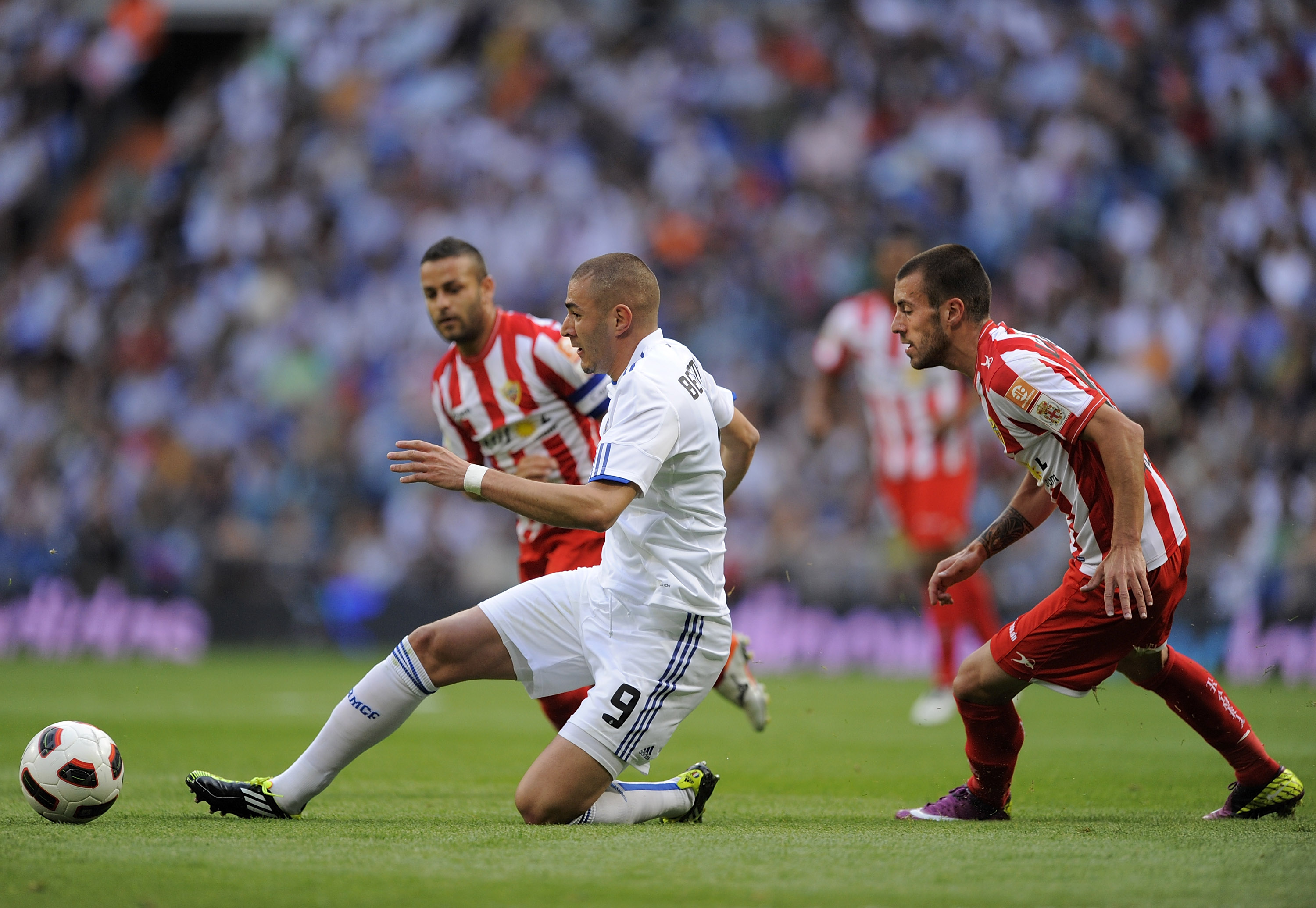 MADRID, SPAIN - MAY 21:  Karim Benzema (L) of Real Madrid passes the ball beside Rigo of UD Almeria during the La Liga match between Real Madrid and UD Almeria at Estadio Santiago Bernabeu on May 21, 2011 in Madrid, Spain.  (Photo by Denis Doyle/Getty Ima