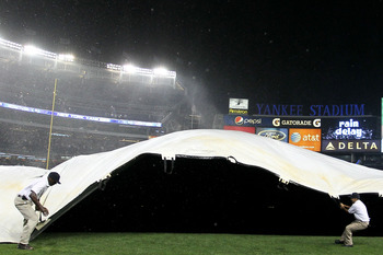 NEW YORK - SEPTEMBER 22:  New York Yankees grounds staff pull over the covers as heavy rains and high winds delayed the game between the New York Yankees and the Tampa Bay Rays during their game on September 22, 2010 at Yankee Stadium in the Bronx borough