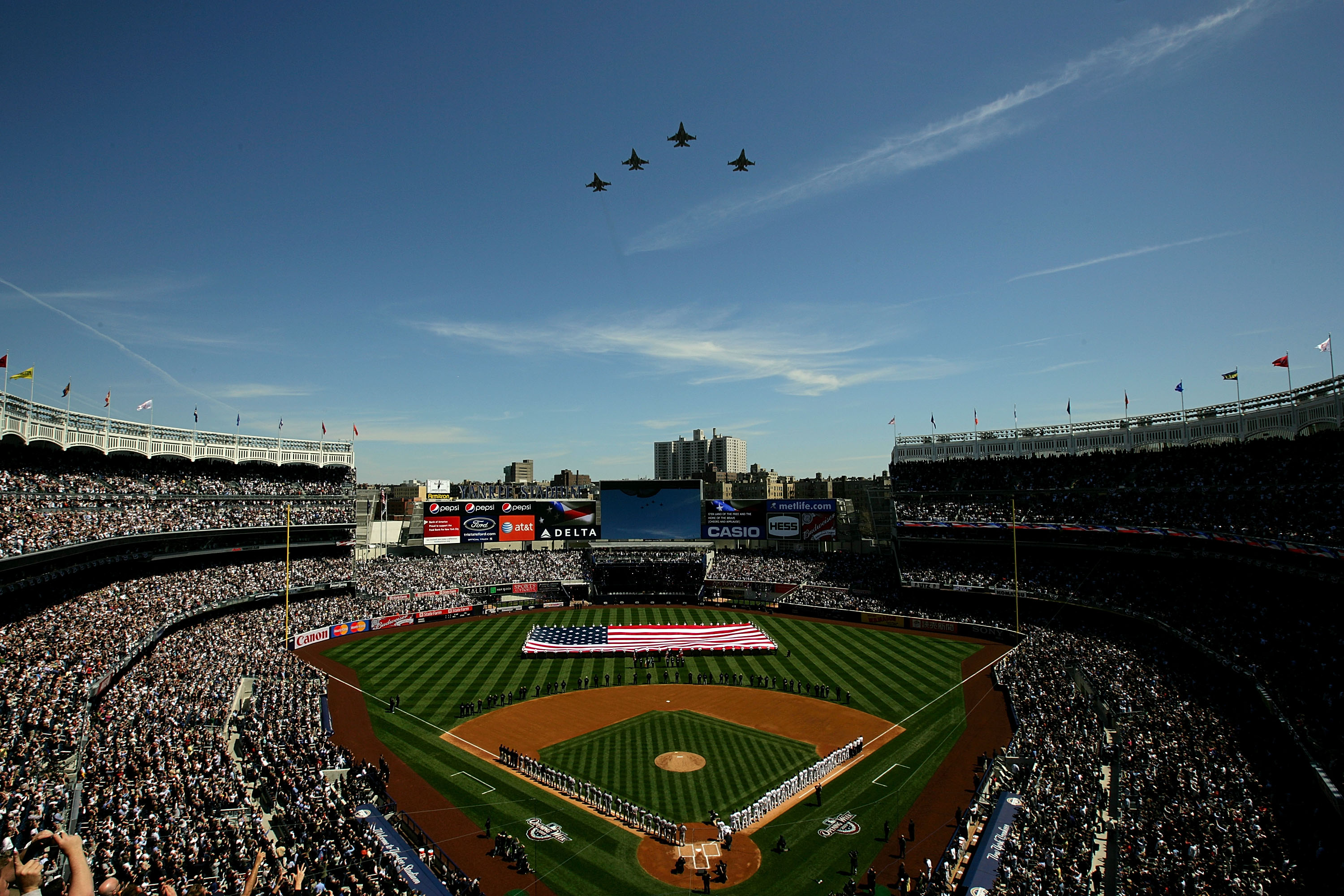 NEW YORK - APRIL 16:  Fighter jets fly over as recording artist Kelly Clarkson sings the National Anthem while members of the military hold a giant American flag before the opening day game between the Cleveland Indians and the New York Yankees at the new