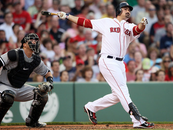 BOSTON, MA - MAY 30:  Adrian Gonzalez #28 of the Boston Red Sox hits a solo home run in the first inning as A.J. Pierzynski #12 of the Chicago White Sox catches on May 30, 2011 at Fenway Park in Boston, Massachusetts.  (Photo by Elsa/Getty Images)