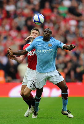 LONDON, ENGLAND - APRIL 16:  Mario Balotelli of Manchester City fights for the ball with Michael Carrick of Manchester United  during the FA Cup sponsored by E.ON semi final match between Manchester City and Manchester United at Wembley Stadium on April 1