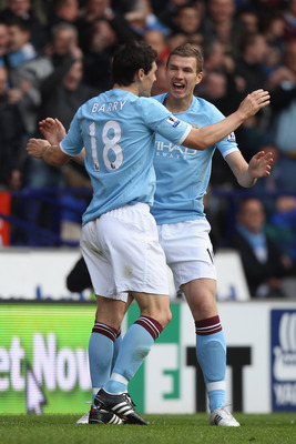 BOLTON, ENGLAND - MAY 22:  Edin Dzeko (R) of Manchester City celebrates scoring the second goal with Gareth Barry (L) during the Barclays Premier League match between  Bolton Wanderers and Manchester City at the Reebok Stadium on May 22, 2011 in Bolton, E