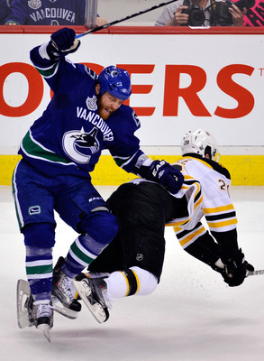 VANCOUVER, BC - JUNE 04:  Raffi Torres #13 of the Vancouver Canucks falls over Daniel Paille #20 of the Boston Bruins during Game Two of the 2011 NHL Stanley Cup Final at Rogers Arena on June 4, 2011 in Vancouver, British Columbia, Canada.  (Photo by Rich