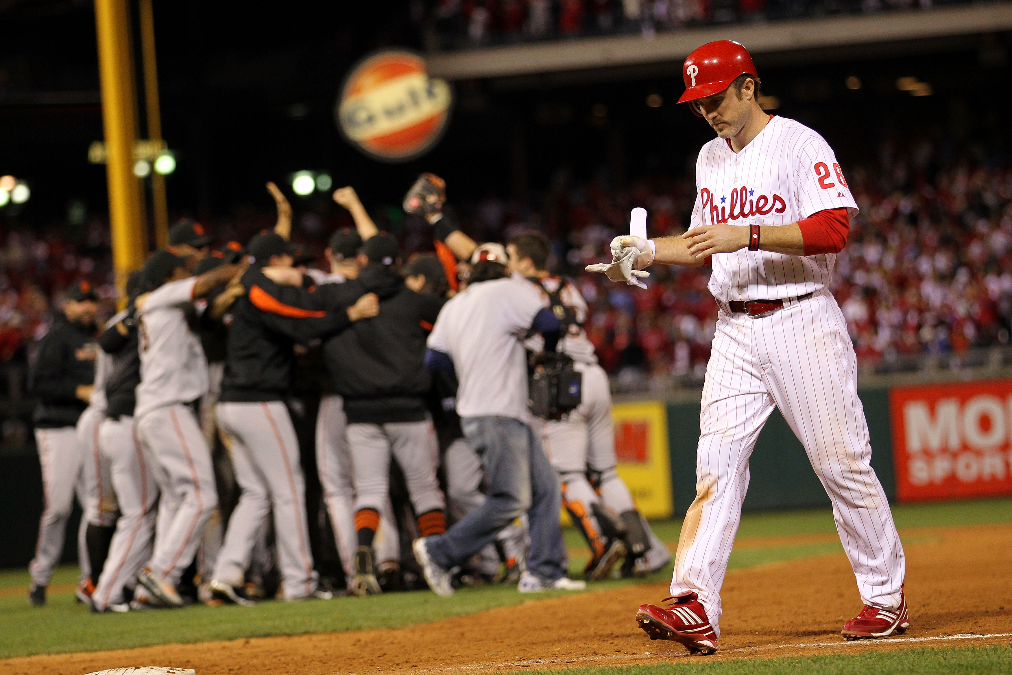 PHILADELPHIA - OCTOBER 23:  Chase Utley #26 of the Philadelphia Phillies walks off the field as the San Francisco Giants celebrate winning 3-2 to win the pennant in Game Six of the NLCS during the 2010 MLB Playoffs at Citizens Bank Park on October 23, 201