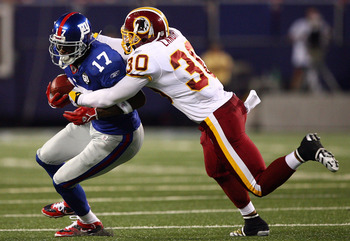 EAST RUTHERFORD, NJ - SEPTEMBER 04:  Plaxico Burress #17 of the New York Giants tries to break the tackle of LaRon Landry #30 of the Washington Redskins at Giants Stadium on September 4, 2008 in East Rutherford, New Jersey  (Photo by Al Bello/Getty Images