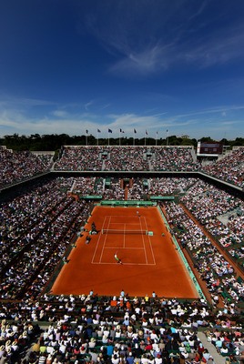PARIS, FRANCE - MAY 28:  Gilles Simon of France serves in front of a packed Court Philippe Chatrier during the men's singles round three match between Mardy Fish of USA and Gilles Simon of France on day seven of the French Open at Roland Garros on May 28,