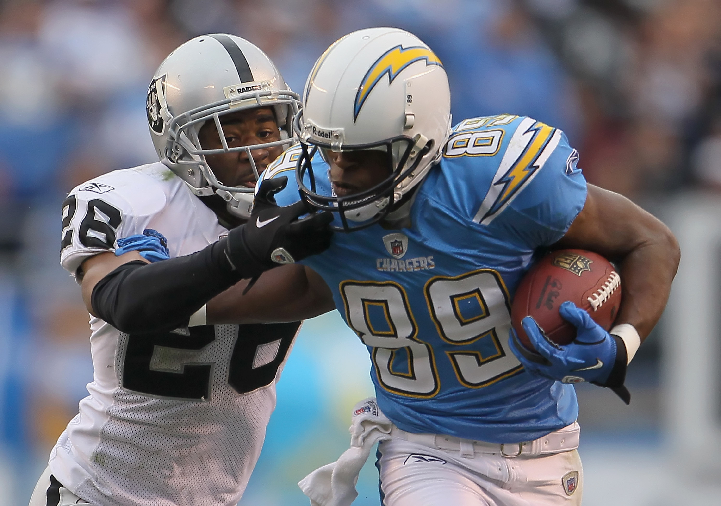 SAN DIEGO - DECEMBER 05:  Stanford Routt #26 of the Oakland Raiders grabs the face mask of Seyi Ajirotutu #89 of the San Diego Chargers in an attempt to bring him down in the third quarter at Qualcomm Stadium on December 5, 2010 in San Diego, California.
