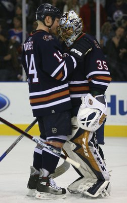 EDMONTON, AB - OCTOBER 12:  Raffi Torres #14 of the Edmonton Oilers congratulates Oilers goalie Dwayne Roloson #35 after the Oilers 6-4 victory over the San Jose Sharks at Rexall Place on October 12, 2006 in Edmonton, Alberta, Canada. Smyth scored three g