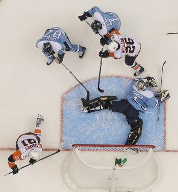 UNIONDALE, NY - NOVEMBER 27:  Brent Johnson #1 of the Pittsburgh Penguins tends net against Matt Moulson #26 and John Tavares #91 of the New York Islanders at the Nassau Coliseum on November 27, 2009 in Uniondale, New York.  (Photo by Bruce Bennett/Getty