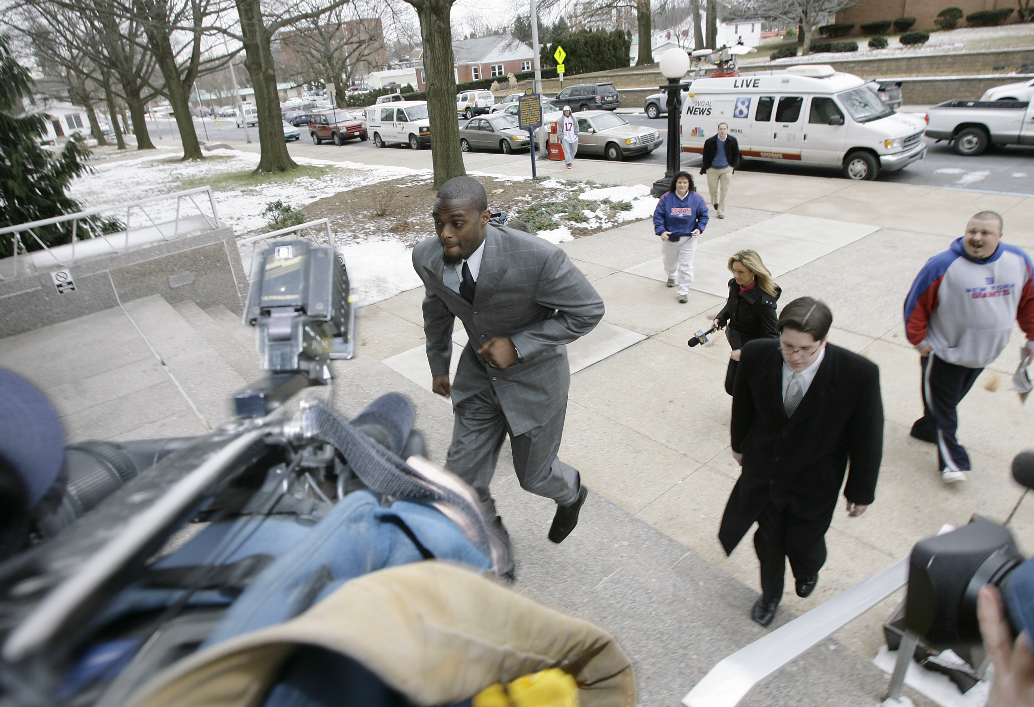 LEBANON - JANUARY 14: New York Giants wide receiver Plaxico Burress runs up the front steps toward members of the media as he arrives at the Lebanon County Courthouse January 14, 2009 in Lebanon, Pa.  Burress is scheduled to appear in a civil trial in a d