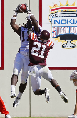 BLACKSBURG, VA - SEPTEMBER 18:  Wide receiver Dwayne Harris #17 of the East Carolina Pirates catches a touchdown pass as cornerback Rashad Carmichael #21 of the Virginia Tech Hokies defends at Lane Stadium on September 18, 2010 in Blacksburg, Virginia.  (