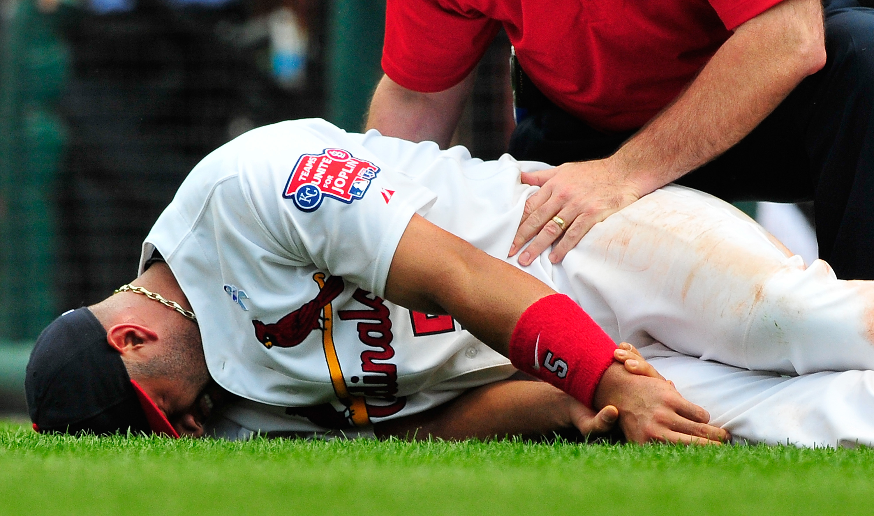 ST. LOUIS, MO - JUNE 19: Albert Pujols #5 of the St. Louis Cardinals holds his wrist after a collision with Wilson Betemit #24 of the Kansas City Royals at Busch Stadium on June 19, 2011 in St. Louis, Missouri.  (Photo by Jeff Curry/Getty Images)
