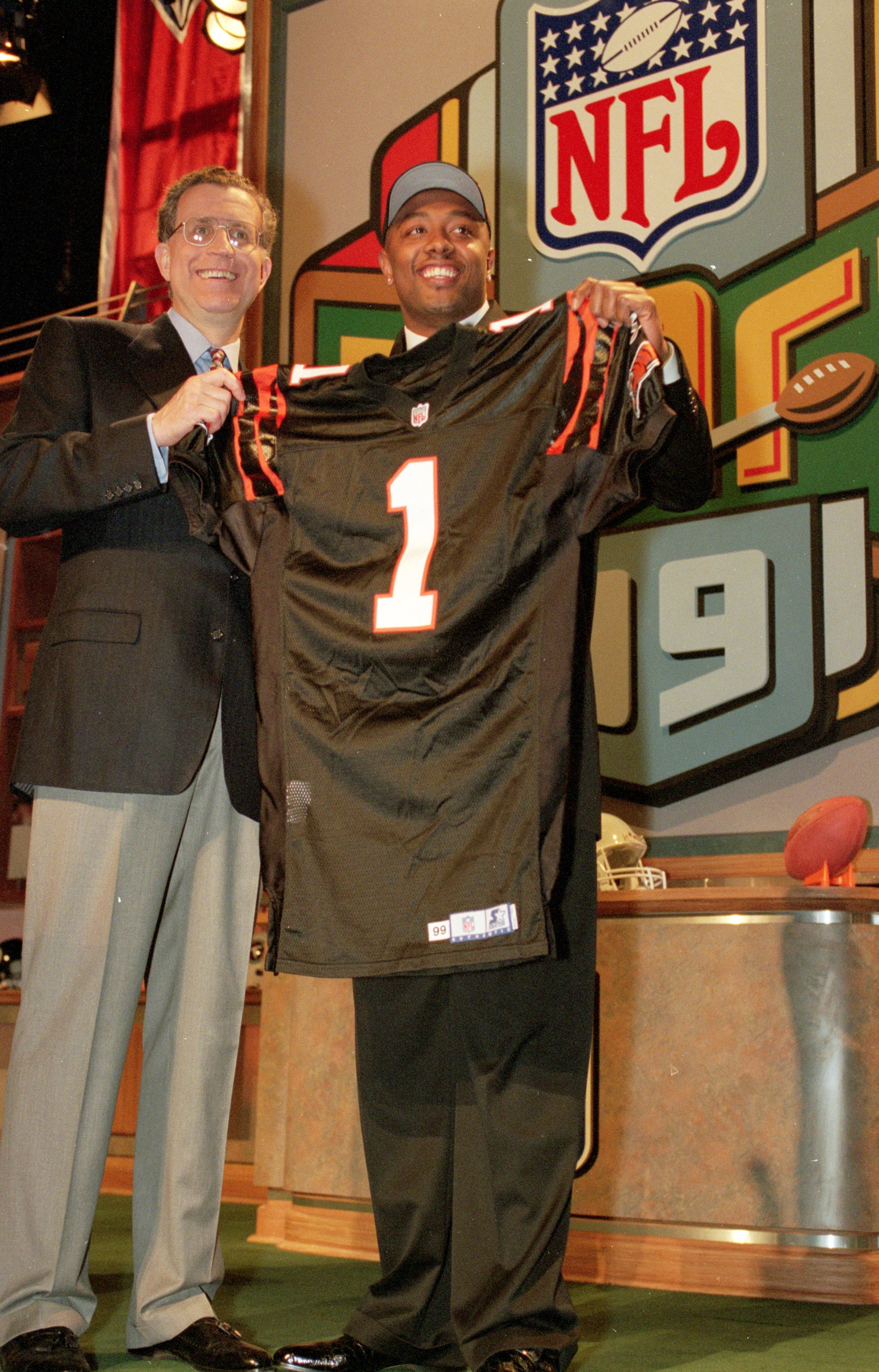 17 Apr 1999:  Akili Smith of the Cincinnati Bengals stands next to the NFL Commisioner Paul Tagliabue and holds up his Bangals jersey during the NFL Draft at Madison Square Garden in New York, New York. Mandatory Credit: Ezra O. Shaw  /Allsport