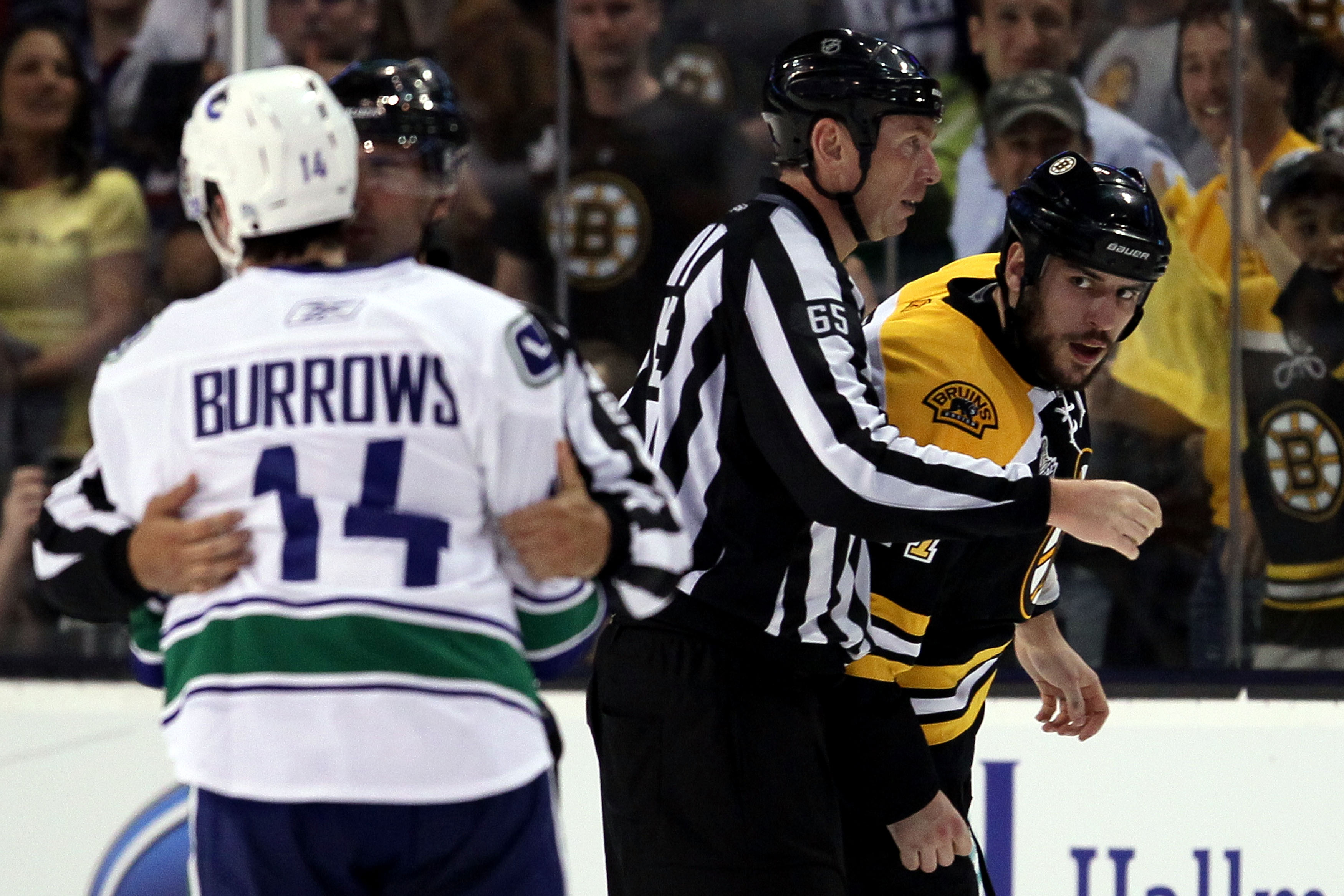 BOSTON, MA - JUNE 06:  Linesman Pierre Racicot #65 breaks up a fight between Milan Lucic #17 of the Boston Bruins and Alex Burrows #14 of the Vancouver Canucks during Game Three of the 2011 NHL Stanley Cup Final at TD Garden on June 6, 2011 in Boston, Mas