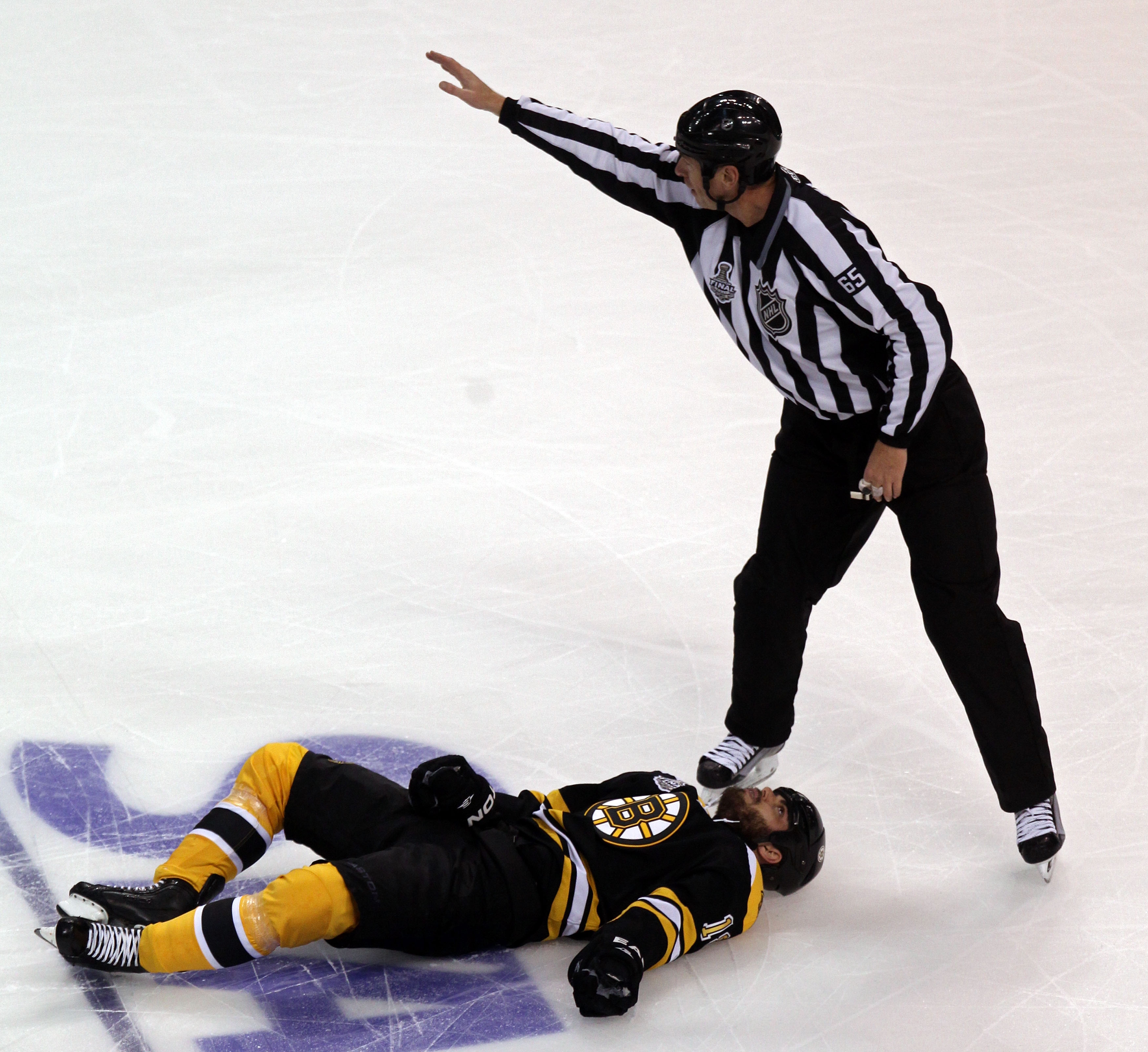 BOSTON, MA - JUNE 06:  Linesman Pierre Racicot #65 calls for assistance for Nathan Horton #18 of the Boston Bruins after being check by Aaron Rome (not pictured) #29 of the Vancouver Canucks during Game Three of the 2011 NHL Stanley Cup Final at TD Garden