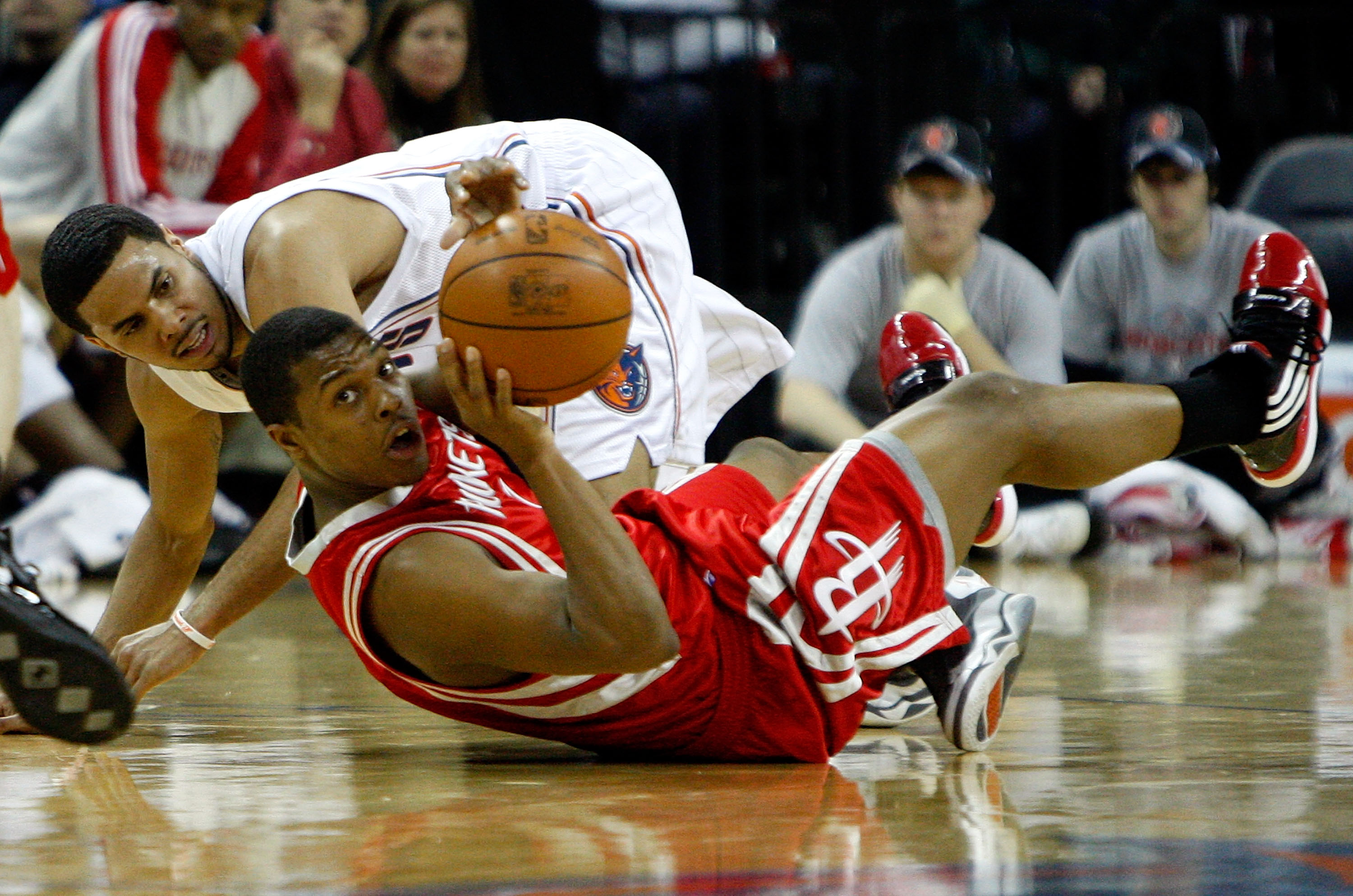 CHARLOTTE, NC - JANUARY 12:  Kyle Lowry #7 of the Houston Rockets scrambles for a loose ball with D.J. Augustin #14 of the Charlotte Bobcats at Time Warner Cable Arena on January 12, 2010 in Charlotte, North Carolina.  NOTE TO USER: User expressly acknowl