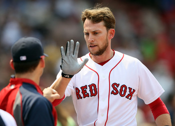 BOSTON, MA - JUNE 01:  Jed Lowrie #12 of the Boston Red Sox is congratulated after he scored in the second inning against the Chicago White Sox on June 1, 2011 at Fenway Park in Boston, Massachusetts.  (Photo by Elsa/Getty Images)
