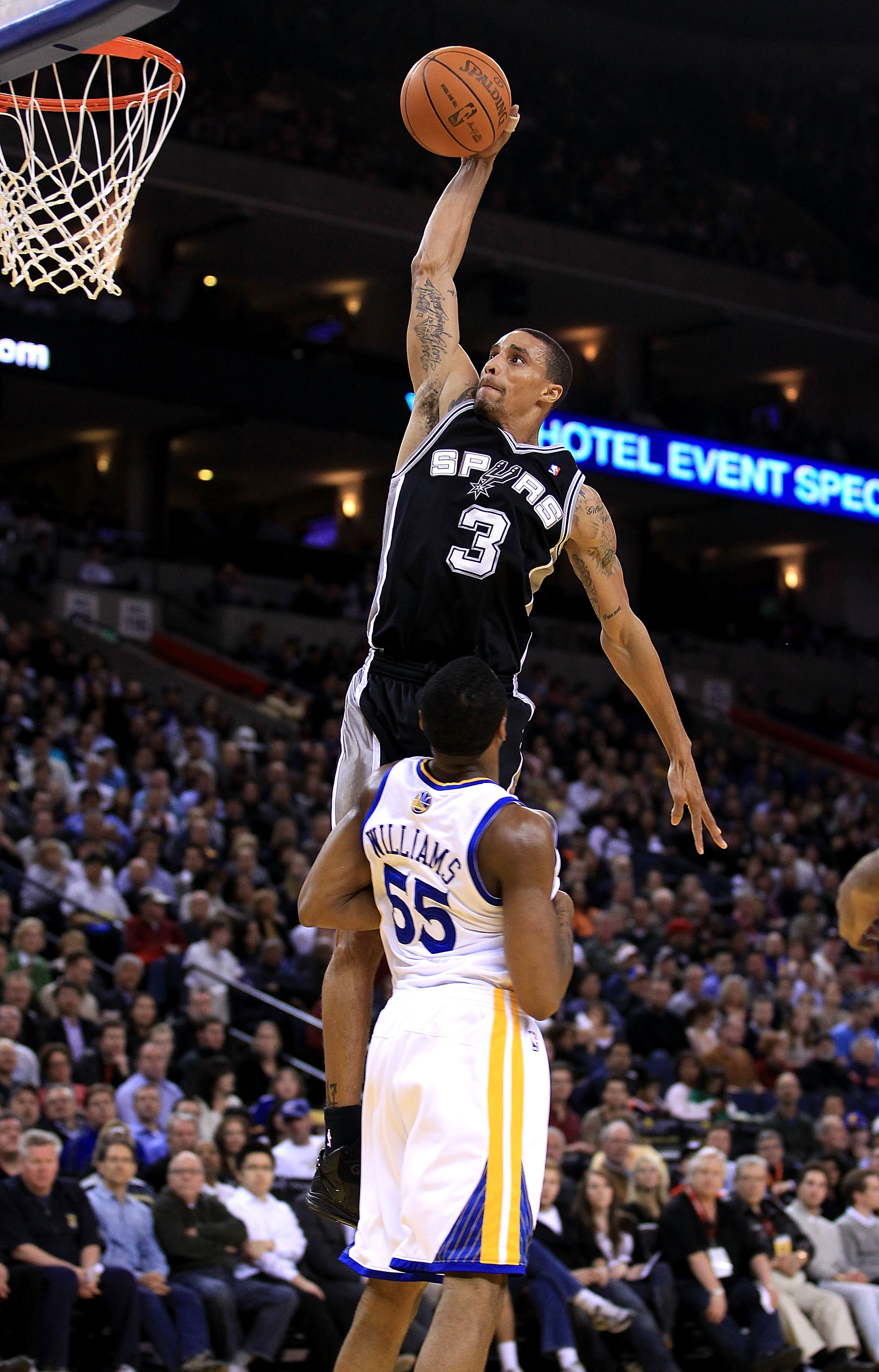 OAKLAND, CA - JANUARY 24:  George Hill #3 of the San Antonio Spurs goes up for a dunk over Reggie Williams #55 of the Golden State Warriors at Oracle Arena on January 24, 2011 in Oakland, California.  NOTE TO USER: User expressly acknowledges and agrees t