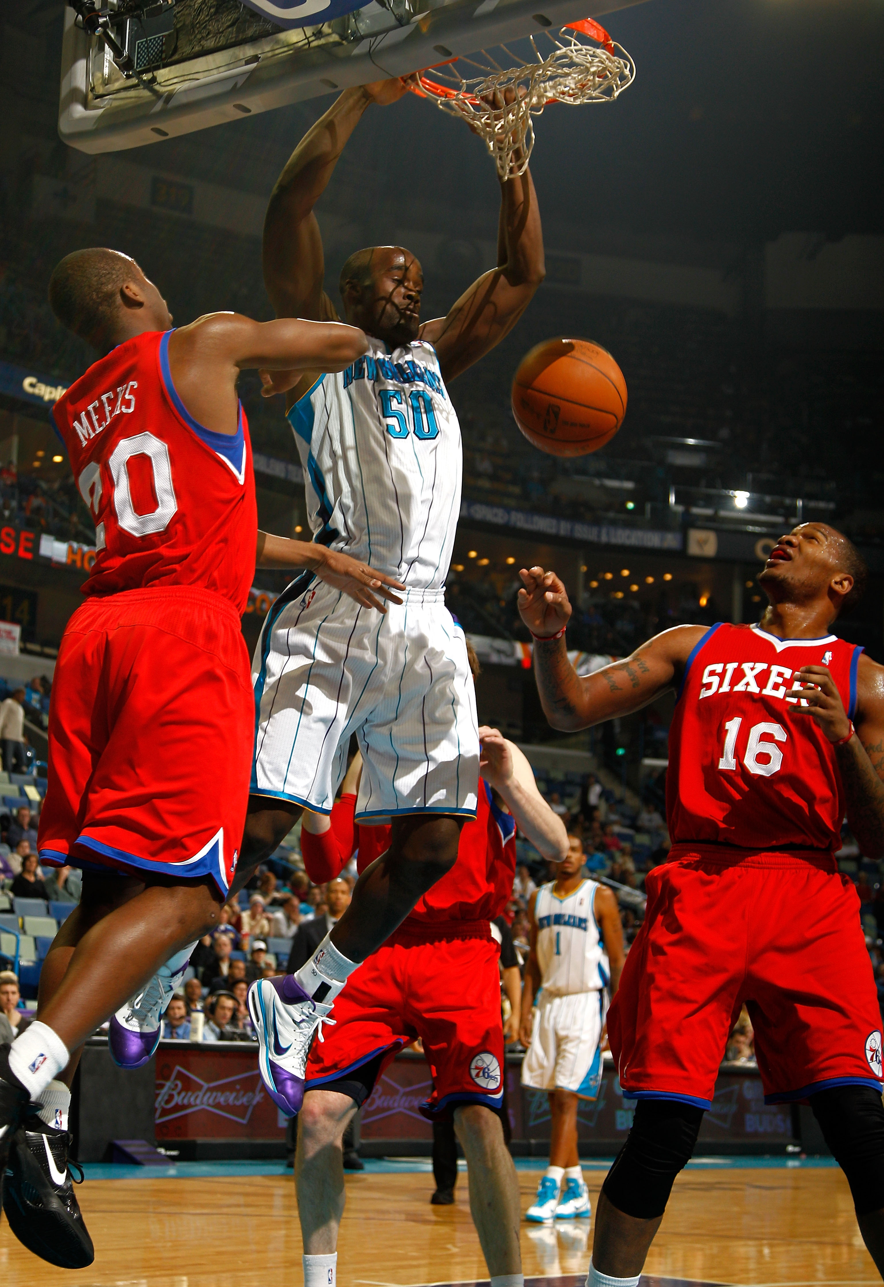 NEW ORLEANS, LA - JANUARY 03:  Emeka Okafor #50 of the New Orleans Hornets dunks the ball between Jodie Meeks #20 and Marreese Speights #16 of the Philadelphia 76ers in the first half at New Orleans Arena on January 3, 2011 in New Orleans, Louisiana. NOTE