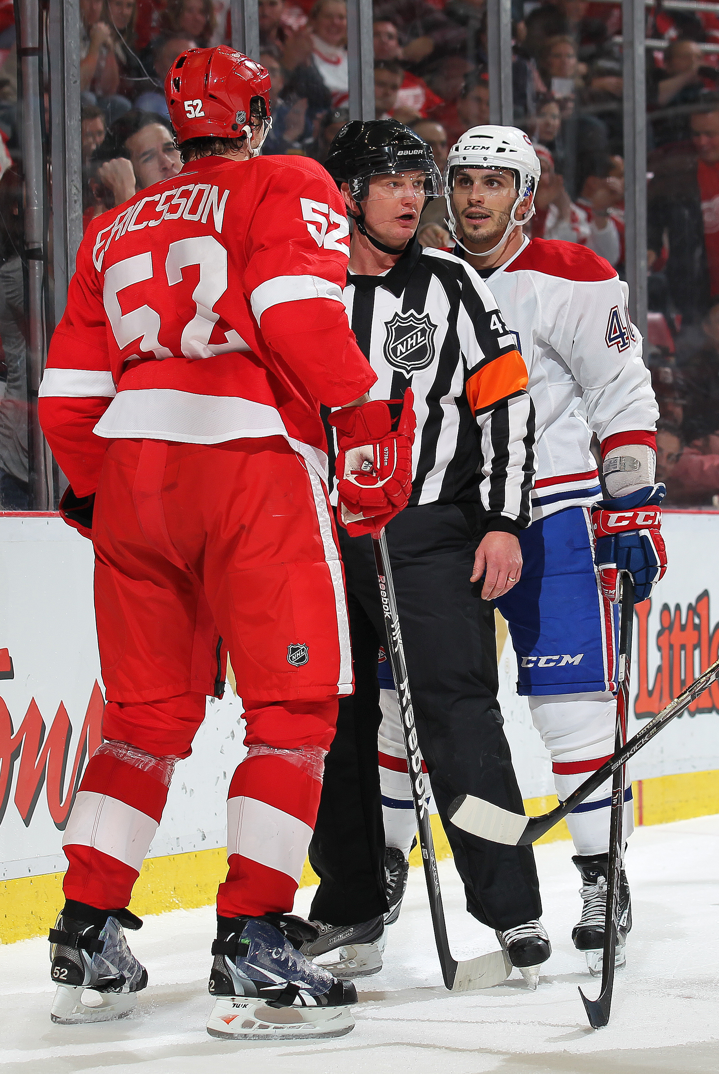 DETROIT,MI - DECEMBER 10:  Maxim Lapierre #40 of the Montreal Canadiens and Jonathan Ericsson #52 of the Detroit Red Wings are separated by a referee during the game at the Joe Louis Arena on December 10, 2010  in Detroit, Michigan. The Wings defeated the