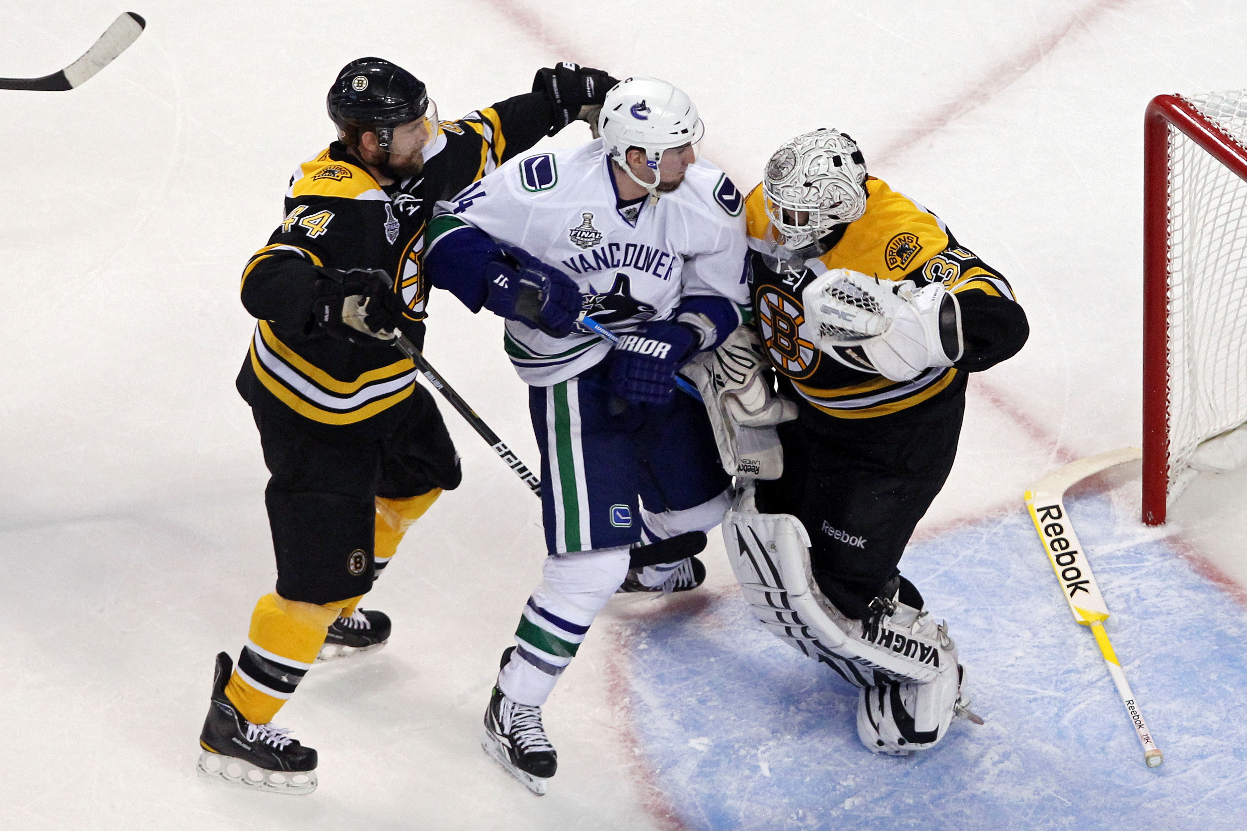BOSTON, MA - JUNE 08:  Dennis Seidenberg #44 of the Boston Bruins  tackles Alex Burrows #14 of the Vancouver Canucks after an incident with Tim Thomas #30 of the Boston Bruins during Game Four of the 2011 NHL Stanley Cup Final at TD Garden on June 8, 2011